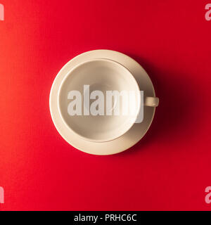 Flat lay view of the one white empty white coffee or tea cup on red color background, closeup, copy space. - Stock Photo