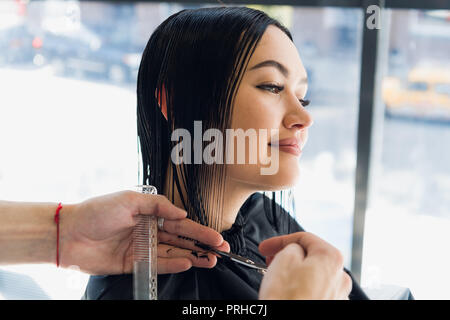 Unrecognizable hairdresser creating hairstyle for beautiful brunette woman - Stock Photo