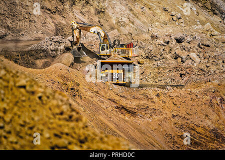 An open pit diamond mine in Botswana with heavy machinery on site. - Stock Photo