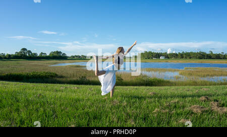 blonde woman spiritual doing yoga king dance standing pulling bow Natarajasana / Dandayamana Dhanurasana pose in nature - Stock Photo