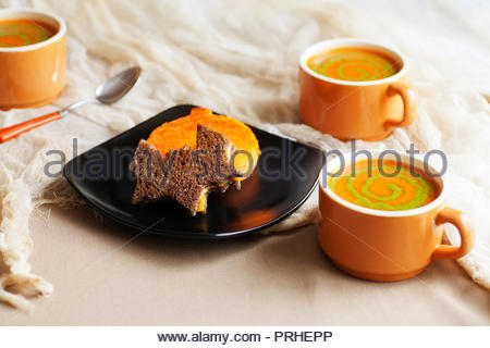 Halloween themed meal. Cutout grilled cheese sandwiches on pumpernickel and orange colored bread. Tomato soup with pesto swirls. - Stock Photo