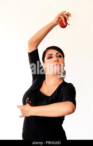 Young Spanish gipsy woman dancing flamenco with brown castanets in her hands. Flamenco dancer in beautiful national dress on a white background. Spain - Stock Photo