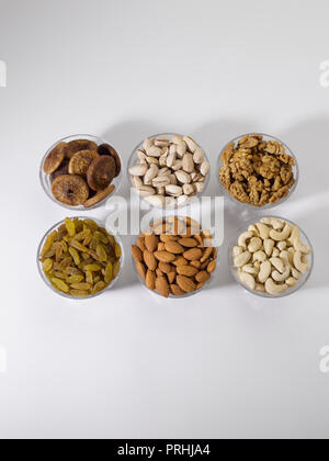 Dryfruits and nuts in six bowls shot against a white background - Stock Photo