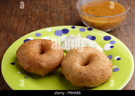 Meduwada in a green plate with sambhar & chutney on a wooden table - Stock Photo