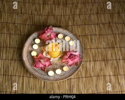 Tray of flowers and candles on a bamboo mat inside a SPA - Stock Photo