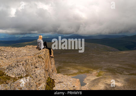 Blond woman sits dangerously alone on the edge of the cliff above the abyss in the mountains of Altai, hanging her legs down over the lake and looking - Stock Photo