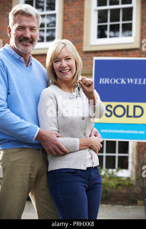 Portrait Of Mature Couple With Keys To New Home - Stock Photo