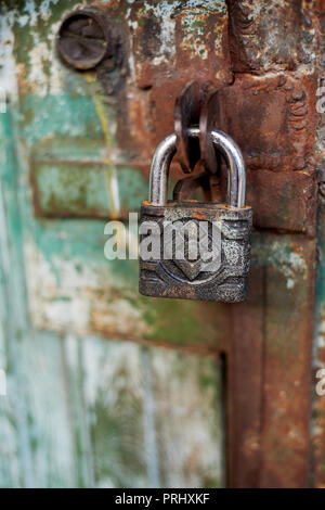 Old metallic padlock on wood,I have not painted the gate. Green shabby paint. - Stock Photo