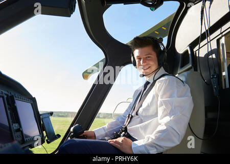Portrait Of Male Helicopter Pilot In Cockpit Before Flight - Stock Photo