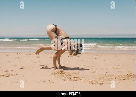 side view of young woman in black bikini practicing Bakasana yoga position on sandy beach - Stock Photo