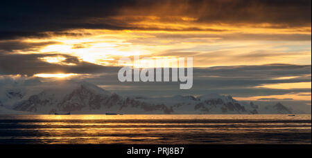 Sunset light through clouds over snow covered mountains, Antarctic Peninsula - Stock Photo