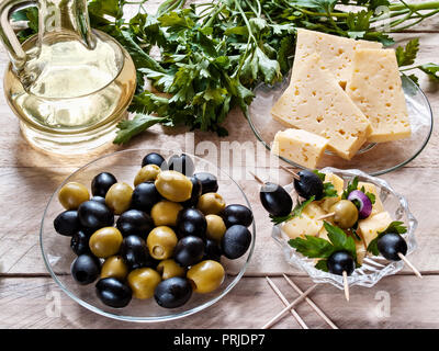 Canape of olives and olives with cheese and greens, olives and cheese in a plate, parsley on a wooden background - Stock Photo