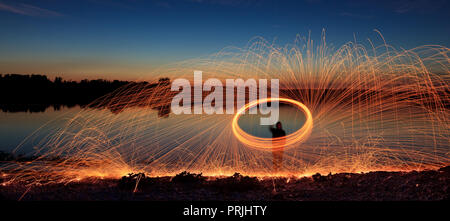 A hoarfrost with sparks at a lake, blue hour, glowing steel wool, long time exposure, Unterallgäu, Swabia, Bavaria, Germany - Stock Photo
