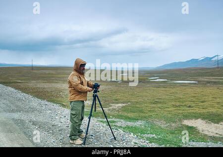 Photographer taking photo on highest mountain Central Asia - Stock Photo