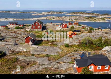 Red wooden houses on the rocky coast, Stockholm archipelago, Huvudskär archipelago island, Sweden - Stock Photo