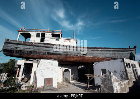 Wooden fishing boat on roof of house two kilometres from the coast, after a December 26, 2004 tsunami in Banda Aceh, Indonesia - Stock Photo