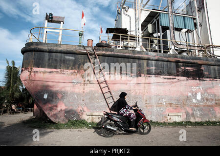Person riding motorbike around electric generator ship moved inland by a 2004 tsunami in Banda Aceh, Sumatra, Indonesia - Stock Photo