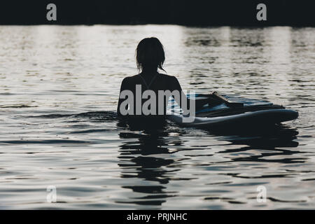 silhouette of woman in water with paddle board - Stock Photo