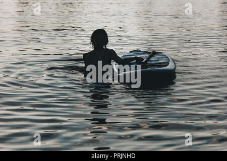 silhouette of woman swimming in water with sup board - Stock Photo