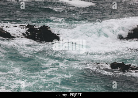 dramatic shot of ocean waves crashing on rocks - Stock Photo