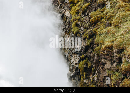 aerial view of fog near mountain covered by moss in Iceland - Stock Photo