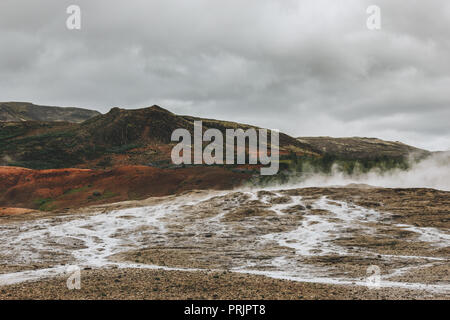 beautiful landscape with volcanic vents under cloudy sky in Haukadalur valley in Iceland - Stock Photo