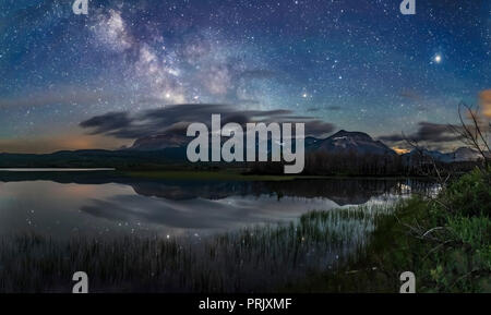 The Milky Way over Maskinonge Lake at Waterton Lakes National Park, Alberta, Canada, on June 17/18, 2018. This was an unusually calm night, allowing t - Stock Photo