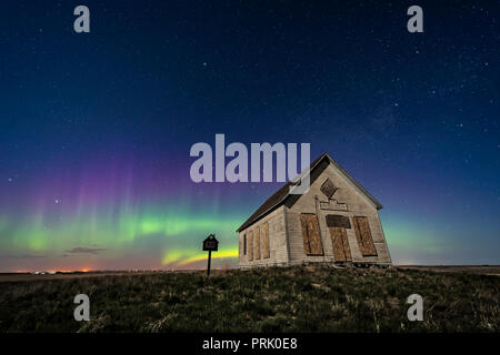 The 1910 Liberty Schoolhouse, a classic pioneer one-room school, on the Alberta prairie under the stars on a spring night, with an aurora dancing to t - Stock Photo