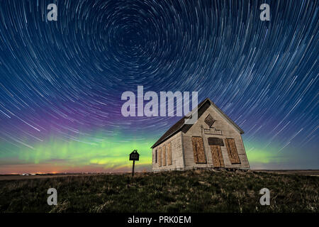 The 1910 Liberty Schoolhouse, a classic pioneer one-room school, on the Alberta prairie under the stars on a spring night, with circumpolar star trail - Stock Photo