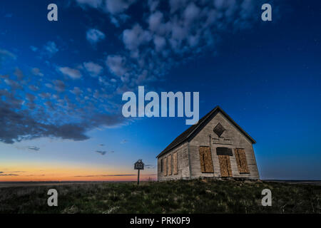 The 1910 Liberty Schoolhouse, a classic pioneer one-room school, on the Alberta prairie under the stars in the twilight of a spring night. Moonlight f - Stock Photo
