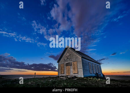 The 1910 Liberty Schoolhouse, a classic pioneer one-room schoolhouse on the Alberta prairie, at sunset as the stars are appearing, and with Venus in t - Stock Photo