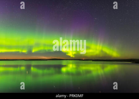 The Northern Lights and a faint display of noctilucent clouds (low on the horizon) over the waters of Crawling Lake in southern Alberta, on June 24/25 - Stock Photo