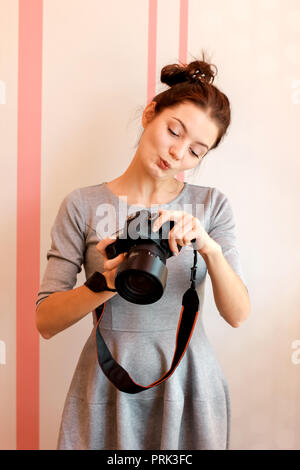 Pretty girl photographer looks into her camera and makes funny f - Stock Photo