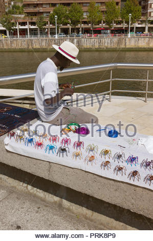 Street vendor making and selling his hand made models of the spider sculpture at the Guggenheim Museum in Bilbao, Spain - Stock Photo