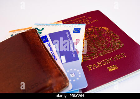 European Union United Kingdom of Great Britain and Northern Ireland burgundy biometric passport with Euro cash notes, EHIC card and driving licence - Stock Photo