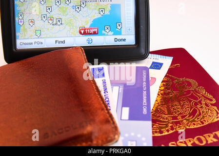 Satnav for Spain with EU United Kingdom of Great Britain and Northern Ireland biometric passport with Euro cash notes, EHIC card, driving licence - Stock Photo
