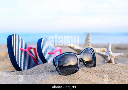 Flip-flops and sunglasses on the beach. At sunset. - Stock Photo
