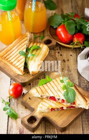 Concept of breakfast. Fruit Juice and delicious fresh Homemade Sandwich with tuna fish, tomatoes, cheese on a wooden kitchen table. - Stock Photo
