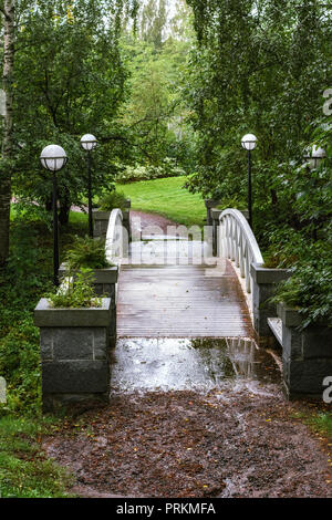 Pedestrian arched bridge over the ravine in the Park with white railing and street lights on the sides. - Stock Photo