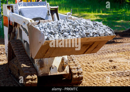 Wheel excavator with hydraulic which is folded into transport position loader dumping gravel - Stock Photo