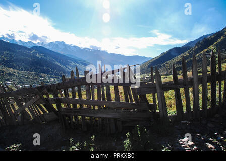 Crooked wooden fence on a sunny mountain landscape in Mestia, Svaneti, Georgia - Stock Photo