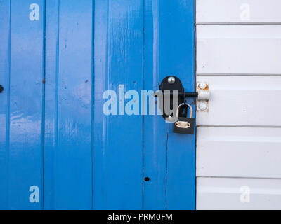 Padlocked door of a beach hut at Newquay, Cornwall. Locked in place, lock in place metaphor. - Stock Photo