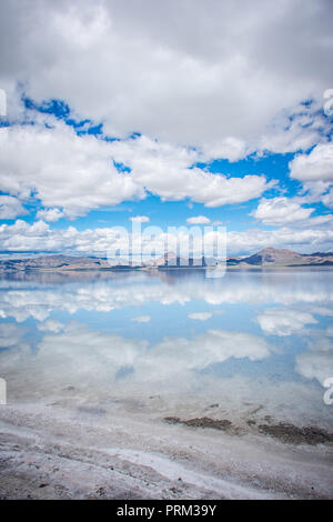 Wide angle view of Bonneville Salt Flats in Utah create a mirror reflection scene on the water, looking surreal - Stock Photo