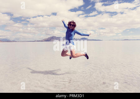 A woman jumps at the Bonneville Salt flats when the salt flats are flooded in the spring. - Stock Photo