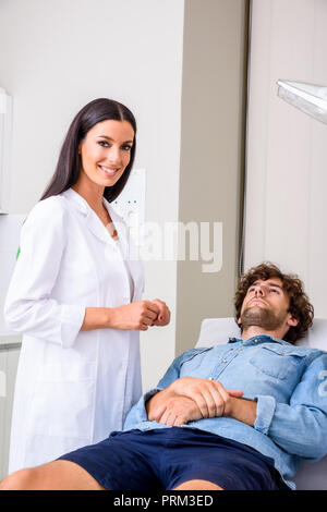 A young male patient in the emergency room getting attended by a female professional physician.