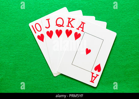 Royal Flush Hearts, a winning hand in a game of poker. Playing cards on a green baize table. - Stock Photo