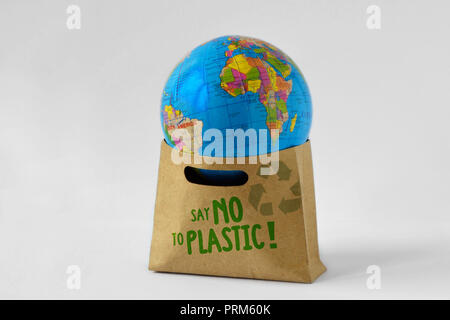 Earth globe in a paper shopping bag with the written Say no to plastic - Ecology concept - Stock Photo