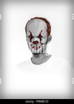 Portrait of scary clown with red make-up, creepy smile in close-up on white background - Stock Photo