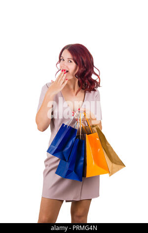 Young redhead woman, wearing pink dress, holding shopping bags, hand covering mouth, surprised emotion isolated on white background. - Stock Photo
