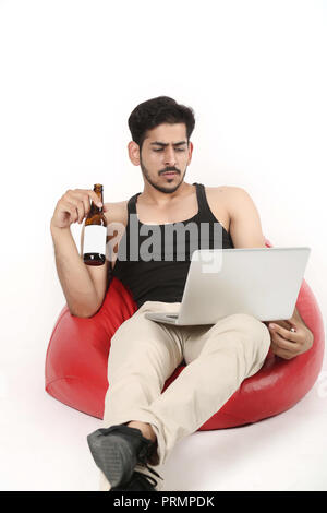 Young boy is sitting on red bean bag couch is seeing laptop with juice bottle in hand. Isolated on white background. - Stock Photo